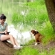 Girl Using Tablet In Park On The Grass With Dog