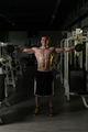 Young Man With Dumbbells Exercising Shoulders