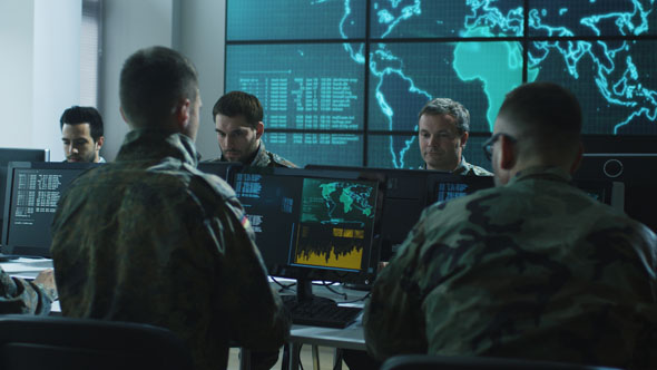 Download Group of Military IT Professionals in Monitoring Room Filled with Displays on Military Base nulled download