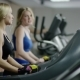 Two Young Blond Women Walking On Treadmill