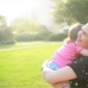 Mother And Child Are Hugging And Having Fun Outdoor In Nature, Happy Cheerful Family. Mother And