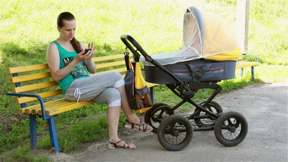 Download Young Mother Sitting In The Park Rolls The Stroller And Looking At Smartphone nulled download
