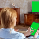 Girl Using Tablet In Front Of The TV 1 With Green Screen