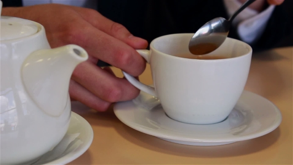 Download Male Hands  Pour Tea Into a Cup And Mixing Spoon nulled download