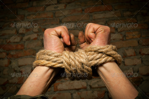 Hands of man tied up with rope - Stock Photo - Images