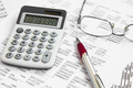 Financial accounting with paper reports and calculator