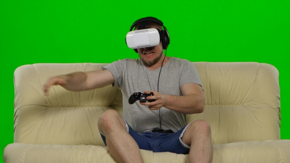 Download Young Handsome Man On Sofa Wearing VR Headset Glasses nulled download