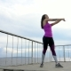 Fitness Girl On The Embankment Of The River. Practice Exercises. .