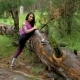 Sporty Girl In The Forest. Perform Stretching. Look At The Camera And Smiling
