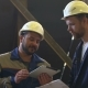 Two Engineers In Hardhats Discussing In Front Of Welding Process