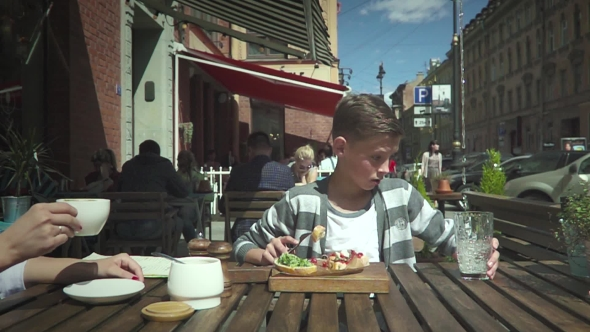 VideoHive Boy Sitting In Outdoor Cafe 17033815