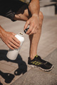 Unrecognizable athlete drinking water after run