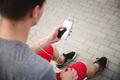 Unrecognizable male athlete with smartphone