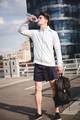 Adult male athlete drinking water after run