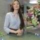 Female Florist Leans On Her Working Desk