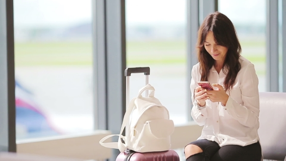 Download Airline Passenger In An Airport Lounge Waiting For Flight Aircraft. Caucasian Woman With Smartphone nulled download