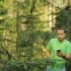 A Man Walks Through the Forest With the Phone