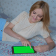Beautiful Girl Using Tablet PC with Pre-Keyed Green Screen Lying on Bed at Home 5