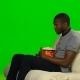 Man With Dark Skin Watching TV And Eating Popcorn. Green Screen