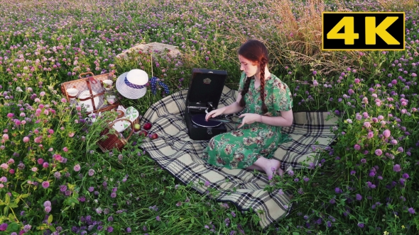 Download Young Girl On Picnic Chooses a Record, Puts It On The Gramophone And Listen nulled download