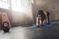 Focused woman stretching on fitness mat