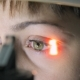 Doctor Optometrist Ophthalmologist Examines The Retina To The Patient Using a Special Instrument,