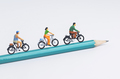 Miniature people cycling on pencil