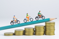 Miniature people cycling on pencil and stack of coins