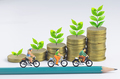 Miniature people cycling on pencil and stack of coins background