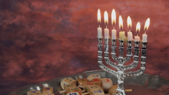 Download Menorah With Candles Over Donuts On Wood Deck For Hanukkah Celebration. nulled download