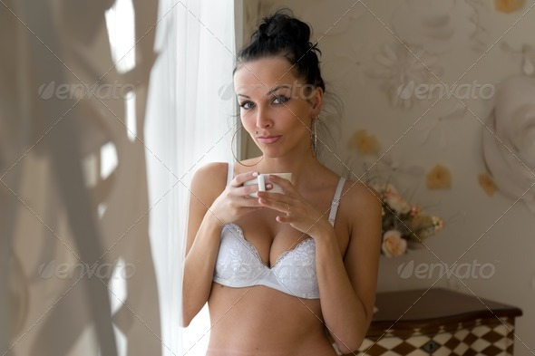 Morning. beautiful woman is drinking tea at the window - Stock Photo - Images