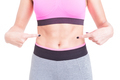 Woman pointing her flat tummy or abs