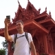 Young Male Traveler Taking Selfie With Asian Buddhist Temple.
