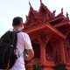 Young Male Traveler Taking Photo Of Asian Buddhist Temple.