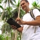 Young Male Traveler Using Tablet In Palm Grove.