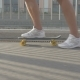 Legs Of Skateboarder To Ride a Skateboard On The Road In The City
