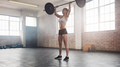 Fit female athlete doing heavy weight lifting