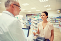 woman giving money to pharmacist at drugstore