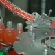 Production Line Conveyor Screw Cap On a Bottle Of Lemonade Soda Mineral Water
