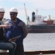 Two Engineers With Laptop Smile And Communicate In Shipping Cargo Port