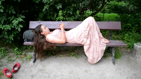 Download Girl Lying On a Bench With Phone nulled download