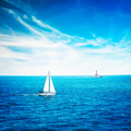 White Yacht Sailing in Calm Blue Sea. Lighthouse.
