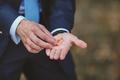 Hands of groom with golden wedding rings.