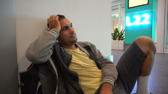 Download Tired Male Traveler Sitting At The Airport nulled download