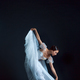 Portrait of the classical ballerina in white dress on black background