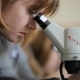 Blonde Woman Looks Into Ocular Of Microscope In Classroom.