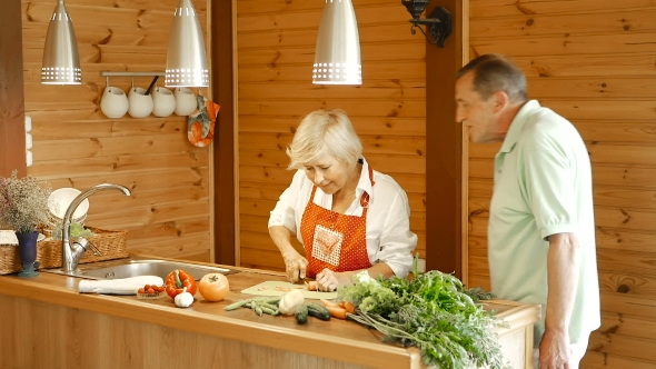 Download Elderly Man Takes Sliced Carrots From The Table. nulled download