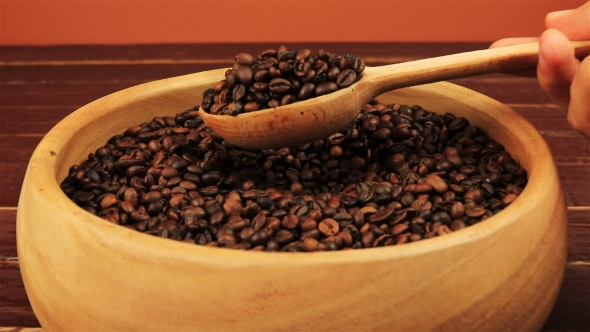 Download Taking Coffee Beans By Using Wooden Spoon In Wooden Bowl On Brown Wooden Table nulled download