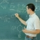 Chemistry Teacher Surrounded Stands Near The Chalkboard In Classroom