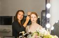 Woman applying makeup to model in salon